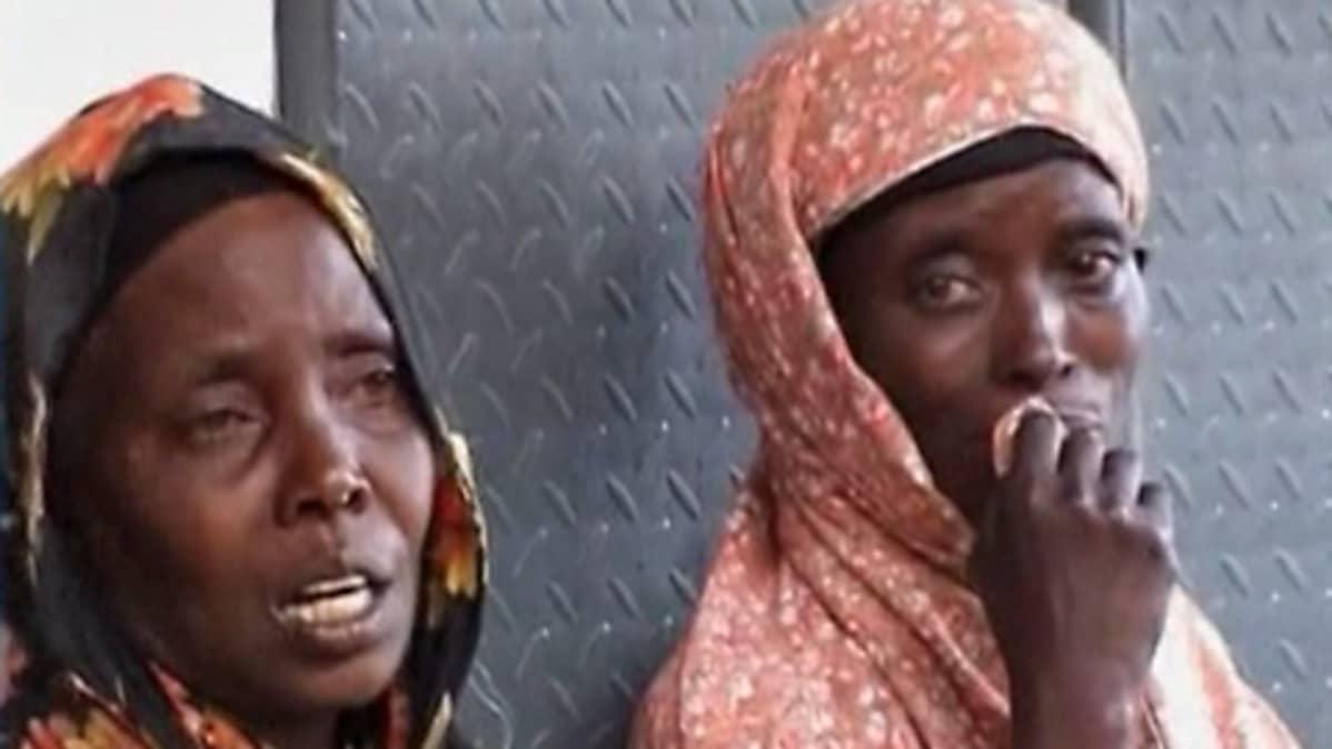 Kaksi itkevää naista nojaa rakennuksen seinään.