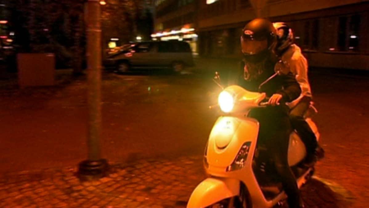 Tyttö ajaa skootterilla öisessä Oulussa, toinen tyttö kyydissä.