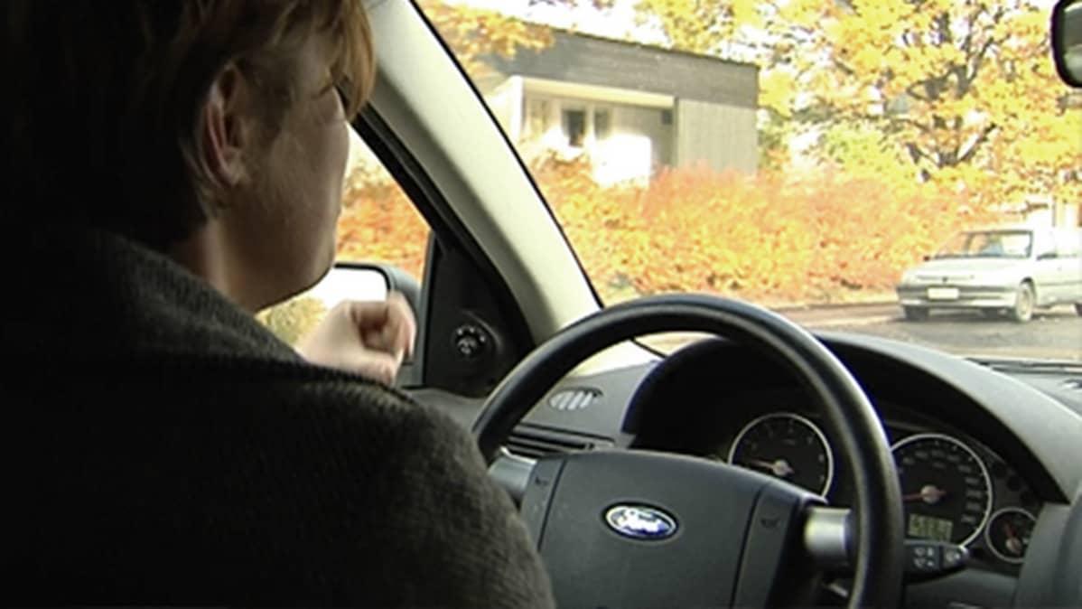 Nuori nainen ajaa autoa.