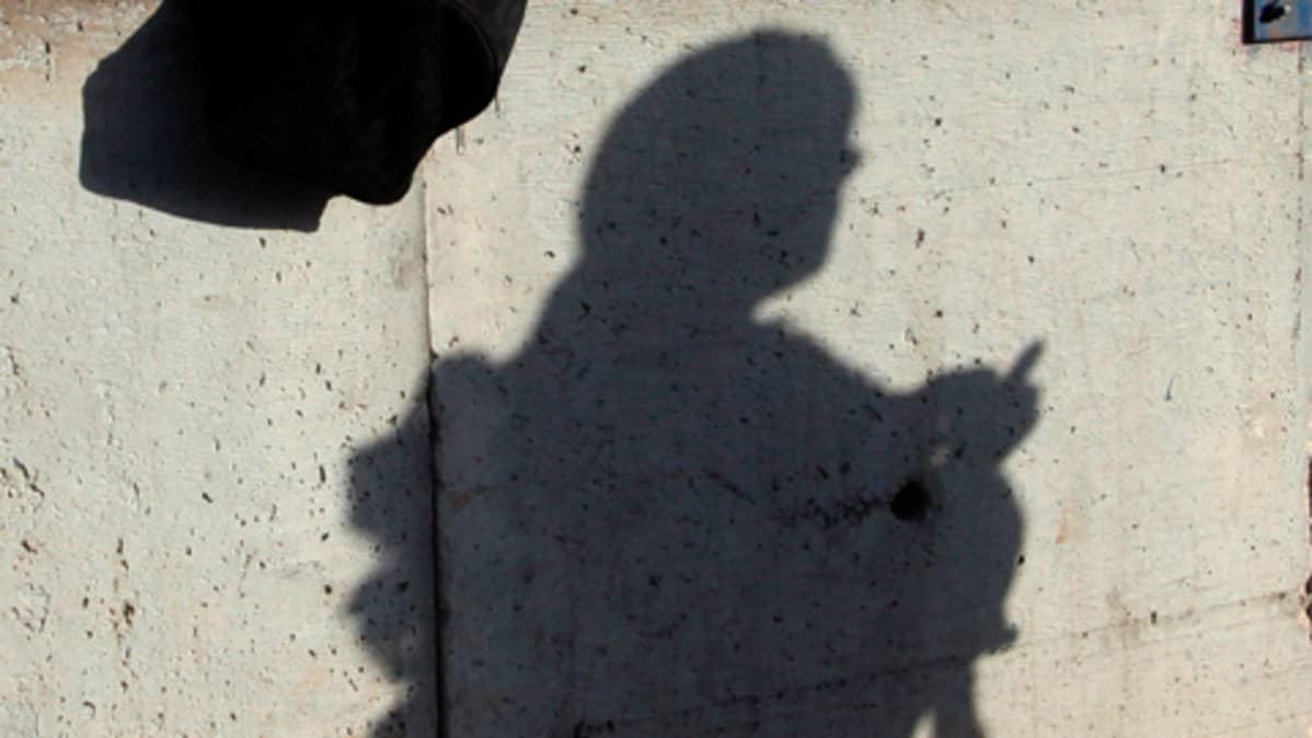 Naisen varjo betoniseinässä.