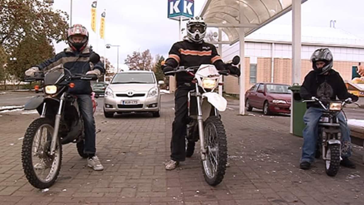 Kolme nuorta mopoilijaa pysähdyksissä kaupan edustalla.