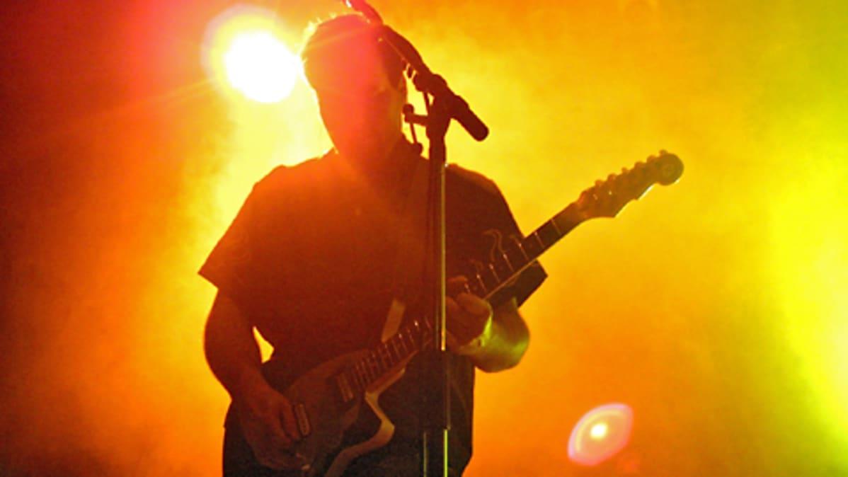 Yhtyeen kitaristi värivalojen ja sumun keskellä.