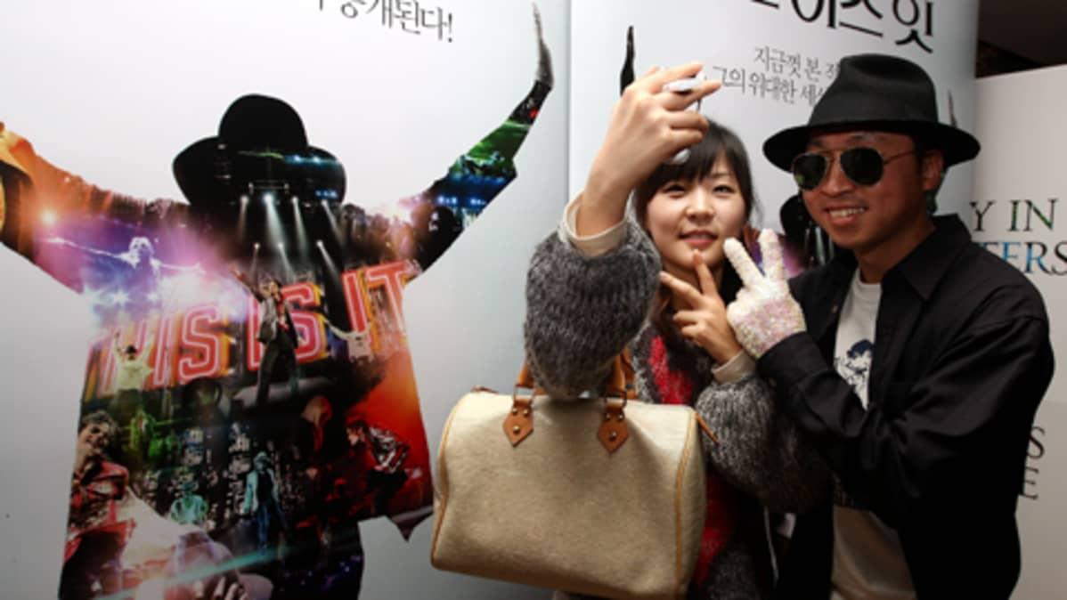 Kaksi eteläkorealaista fania kuvaavat itseään Michael Jackson-elokuvajulisteiden edessä.