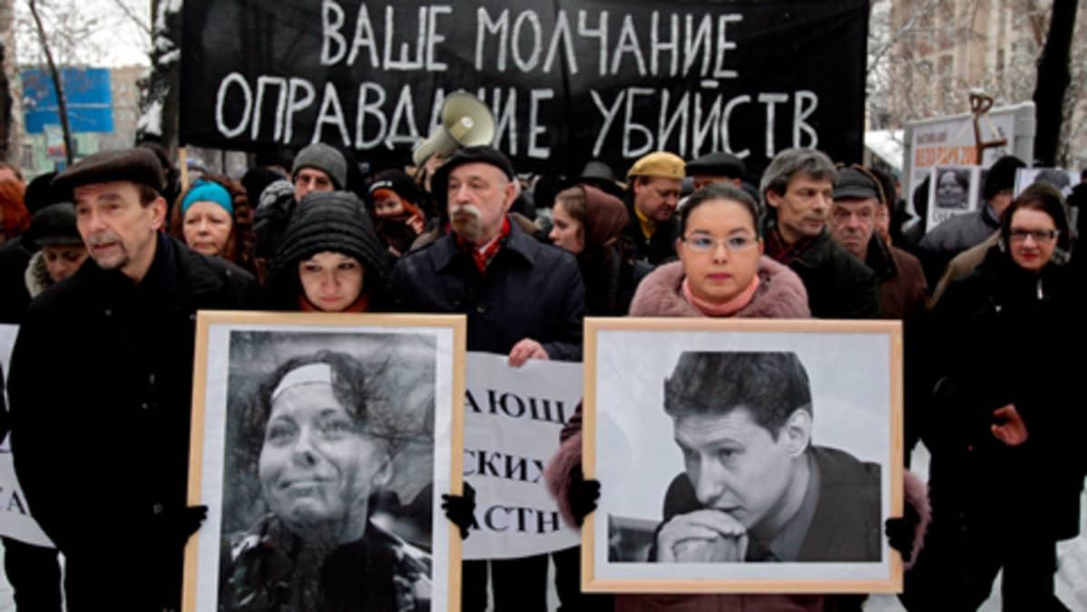 ihmiset kantavat musta banderollia ja tapettujen valokuvia