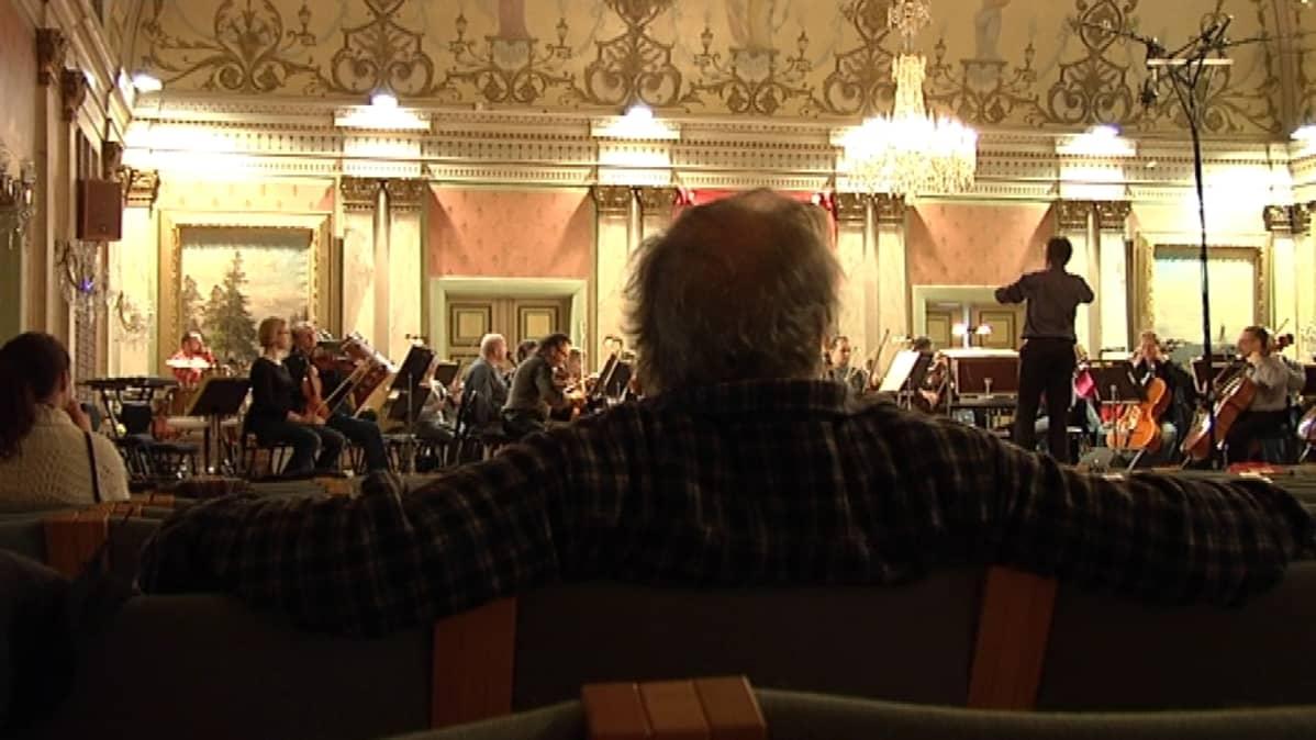 Näkymä  Vaasan kaupungintalon juhlasalissa. Orkesteri lavalla.