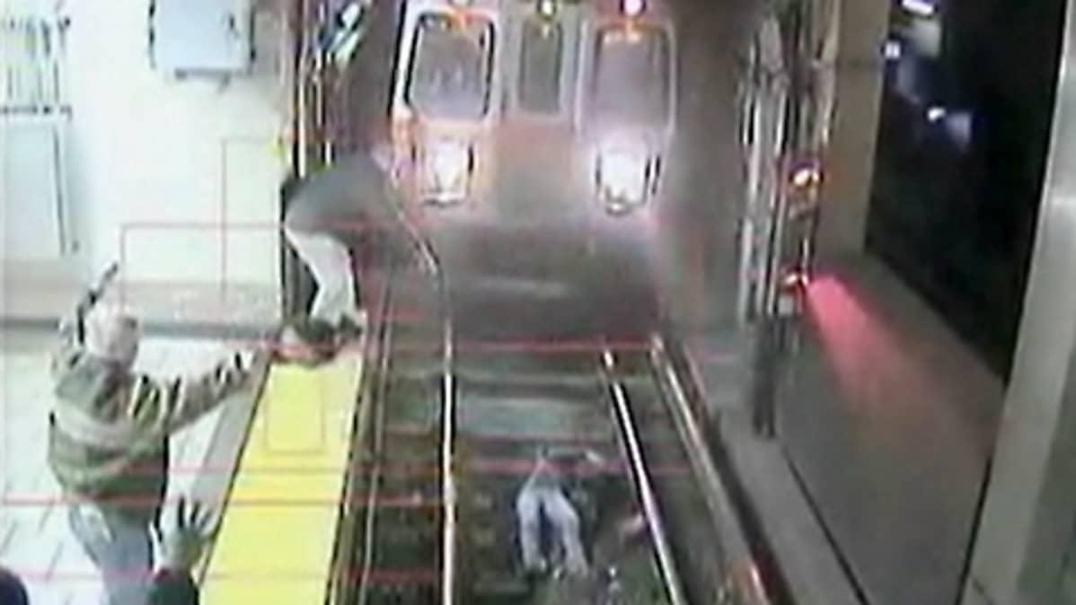 Metrojuna lähestyy raiteille pudonnutta naista