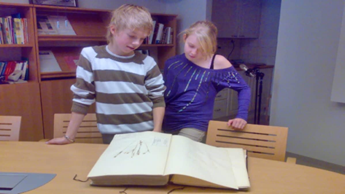 Kaksi oppilasta tutkii kasvistoa.
