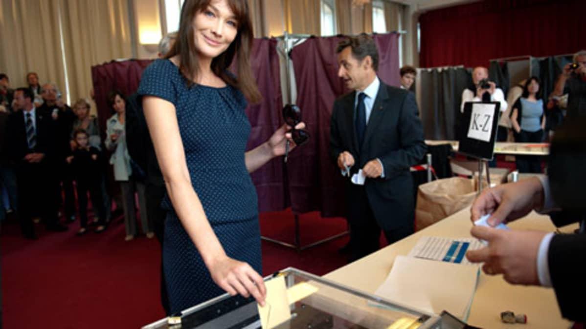 Poseeraava Bruni pudottamassa äänestyslappua uurnaan, Sarkozy taustalla