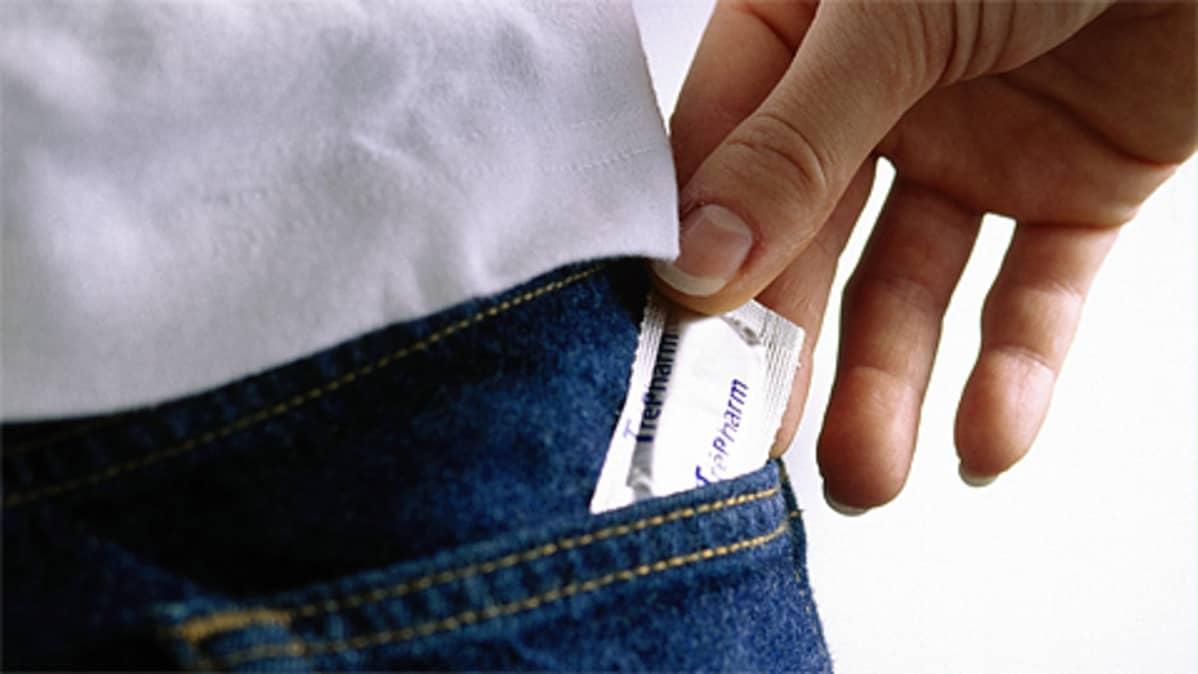 Nainen laittaa kondomia takataskuun