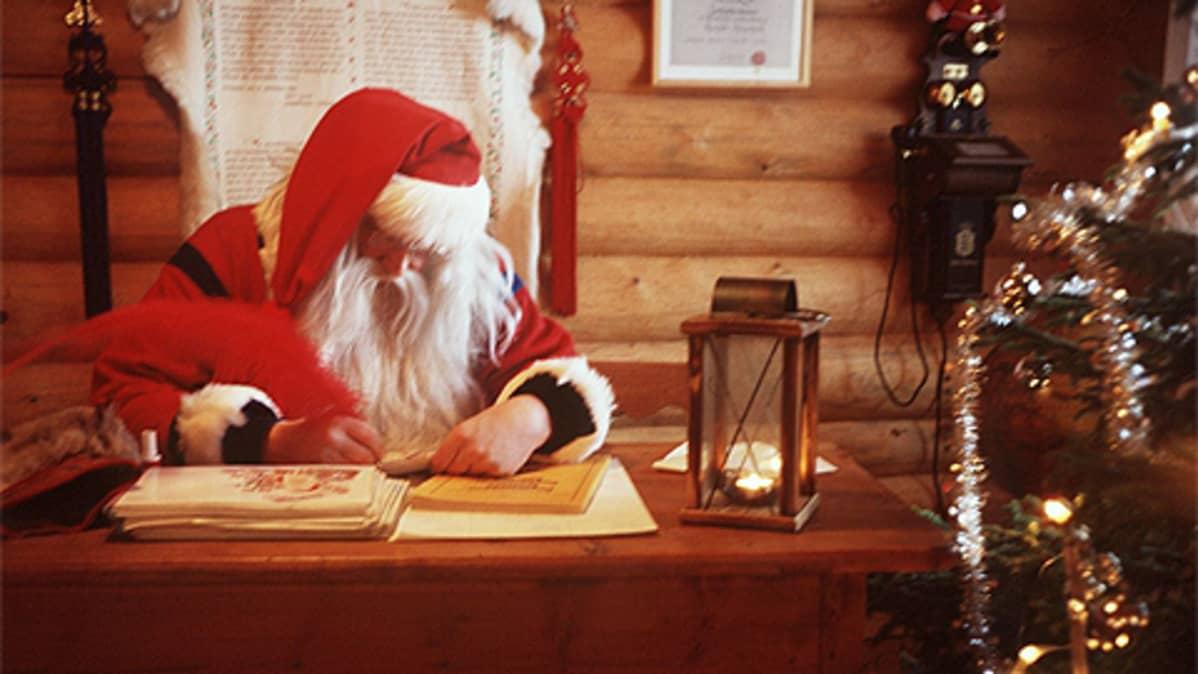 Joulupukki kirjoittaa vastausta lapsen kirjeeseen.