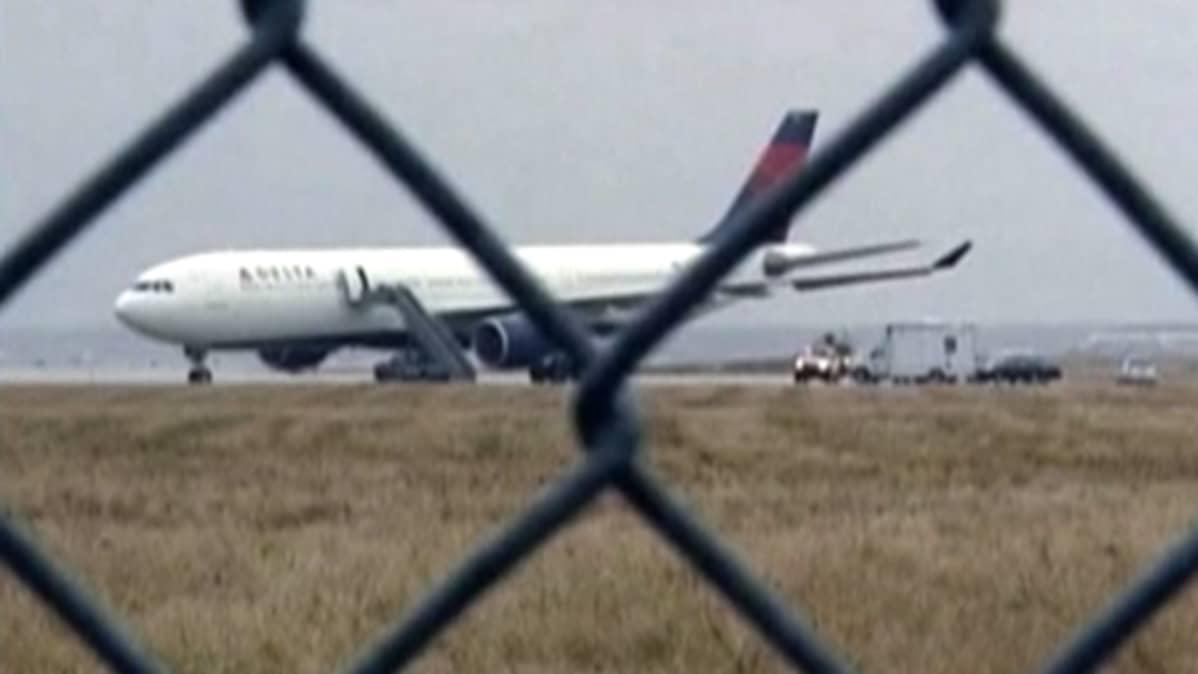 Verkkoaidan takaa kuvattu kone lentokentällä.