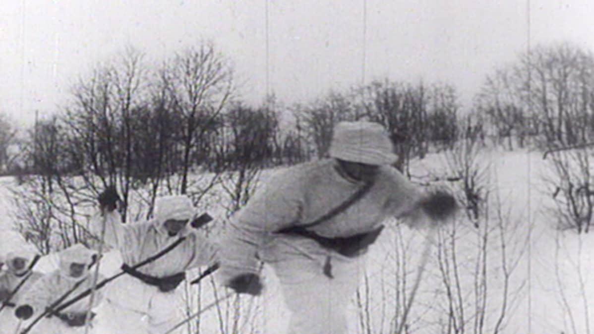 Lumipukuiset miehet hiihtävät.