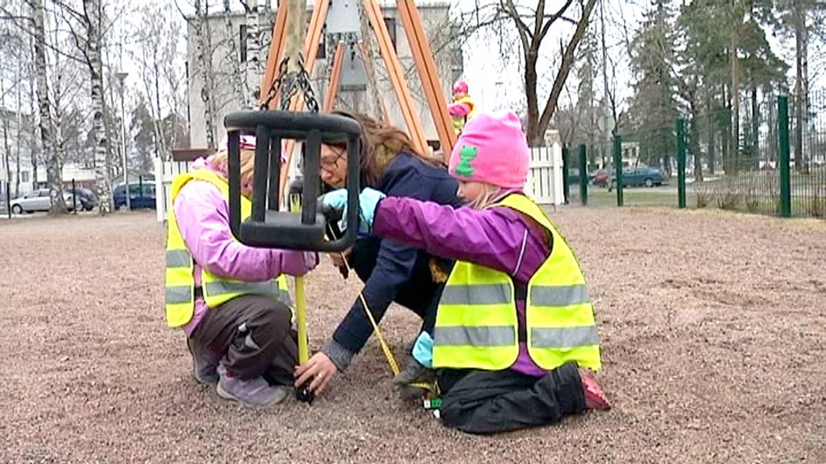 tytöt mittaavat keinun korkeutta.