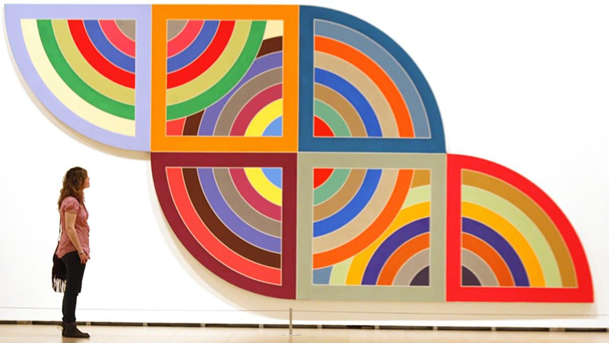 Nainen katselee Frank Stellan maalausta Bilbaon Guggenheim-museossa.