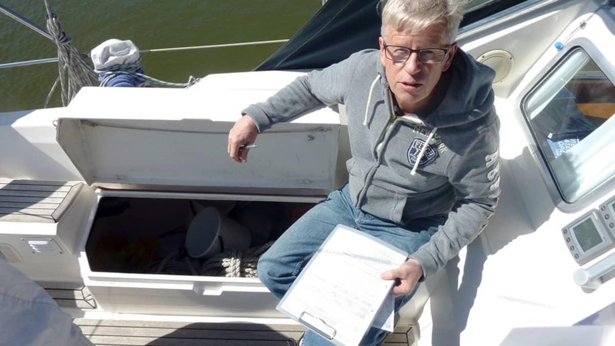 Teijo istuu veneen penkillä.
