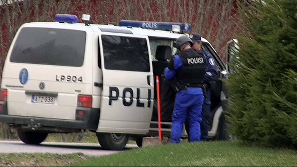 Poliisiauto ja kaksi poliisia keskustelemassa auton avoimen oven luona.