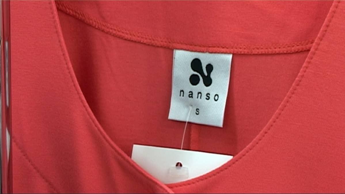 Nanson logo punaisessa paidassa
