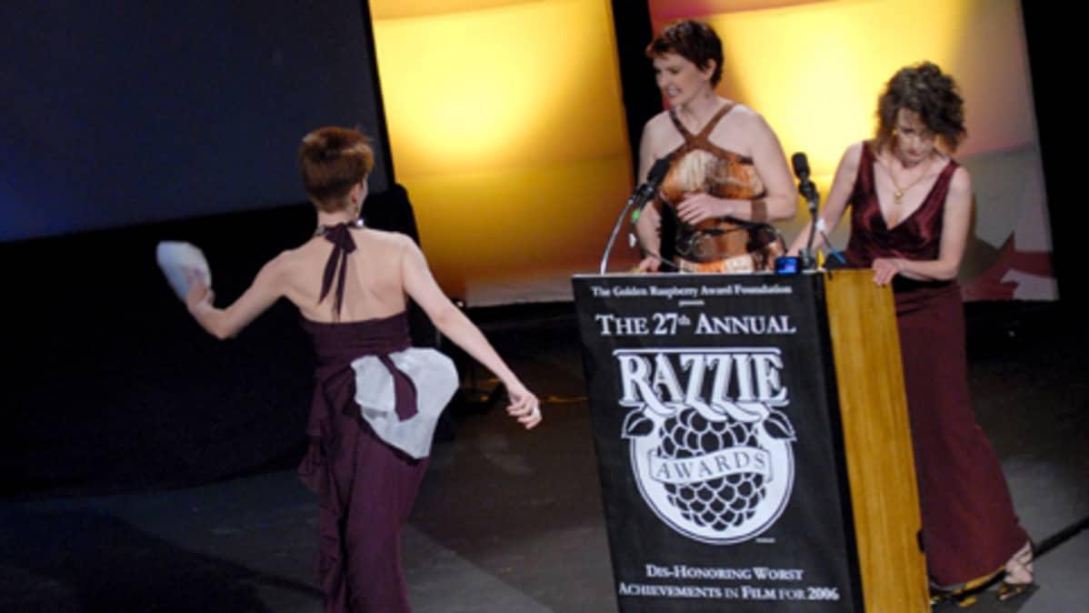 Alta McGovern tuo kirjekuorta Rebecca Marcottelle ja Kelie McIverille vuosittaisessa Razzie-palkintojenjakotilaisuudessa.