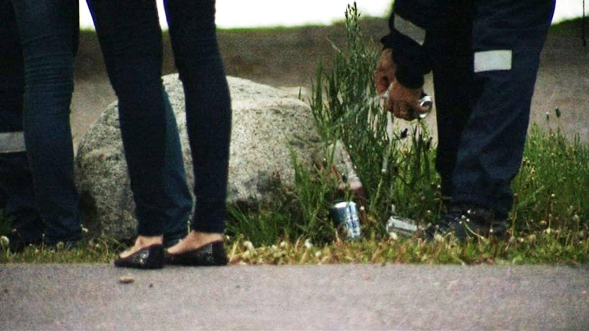 Police empty cans of underage drinkers at Hietaniemi beach. Poliisi hävitti päättäjäisviikonloppuna yli tuhat litraa vähemmän alholia kuin viime vuonna.
