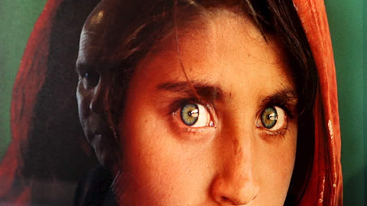 Afgaanityttö valokuvassa, joka lasin pinnasta heijastuu toiset kasvot
