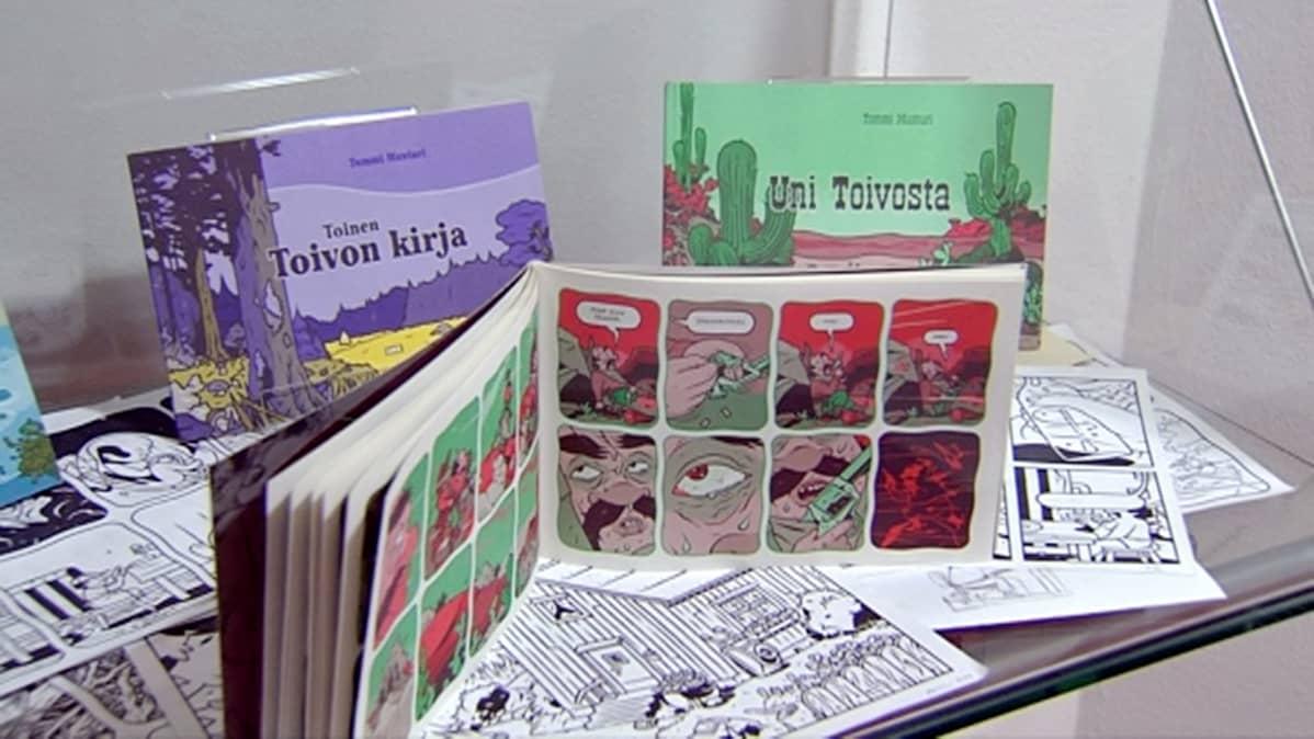 Tommi Musturin Toivon kirja -sarjakuvia lasivitriinissä.