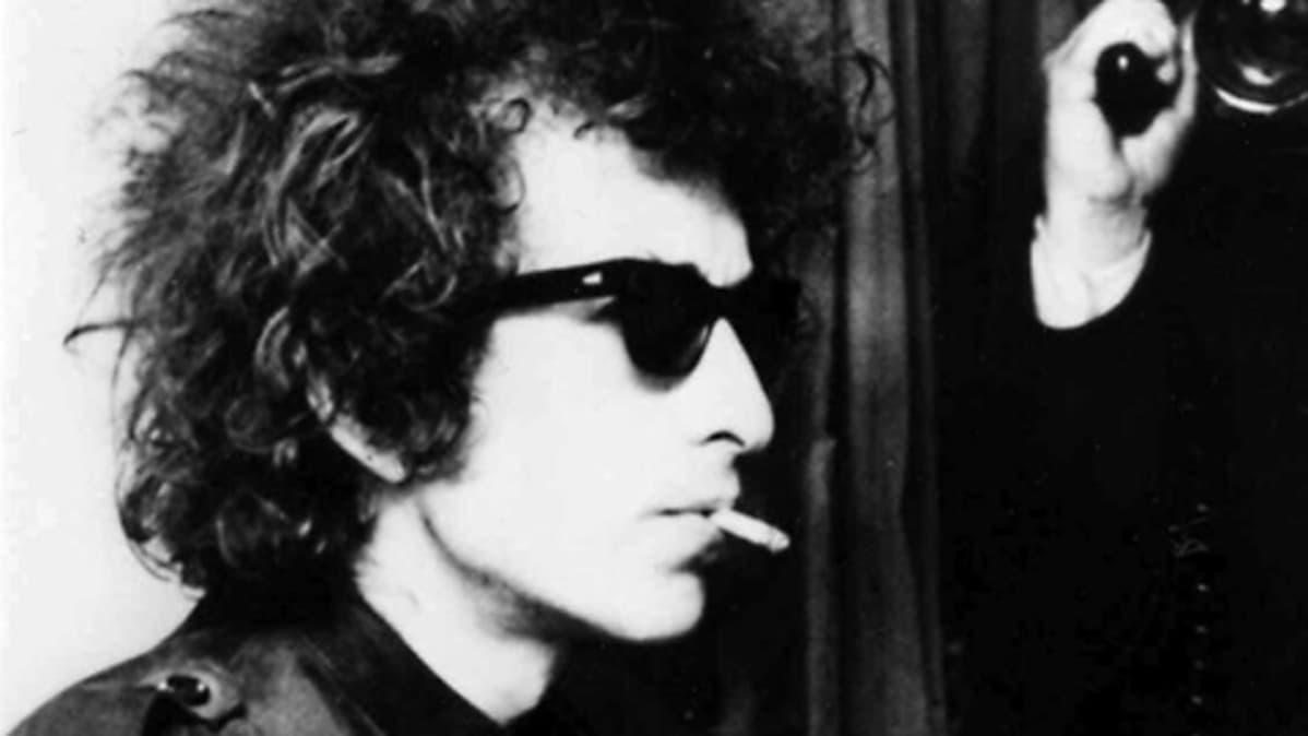 Bob Dylan tupakka suussa ja aurinkolasit silmillään. Taustalla mies kuvaa elokuvakameralla.