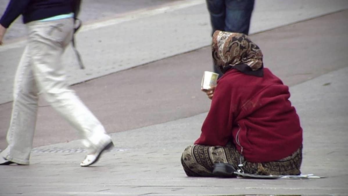 Kerjäläinen istuu kuppi kädessä ihmisten kävellessä ohi.
