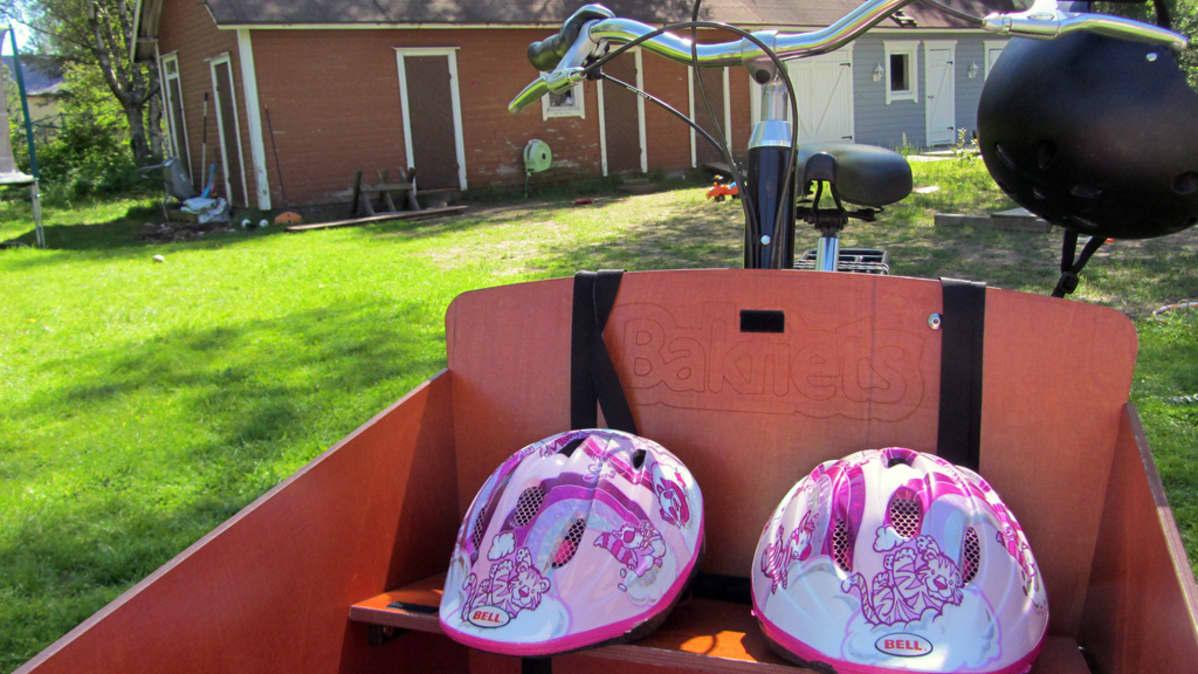 Kuvassa tavarafillari ja kaksi lasten pyöräilykypärää sekä aikuisten kypärä