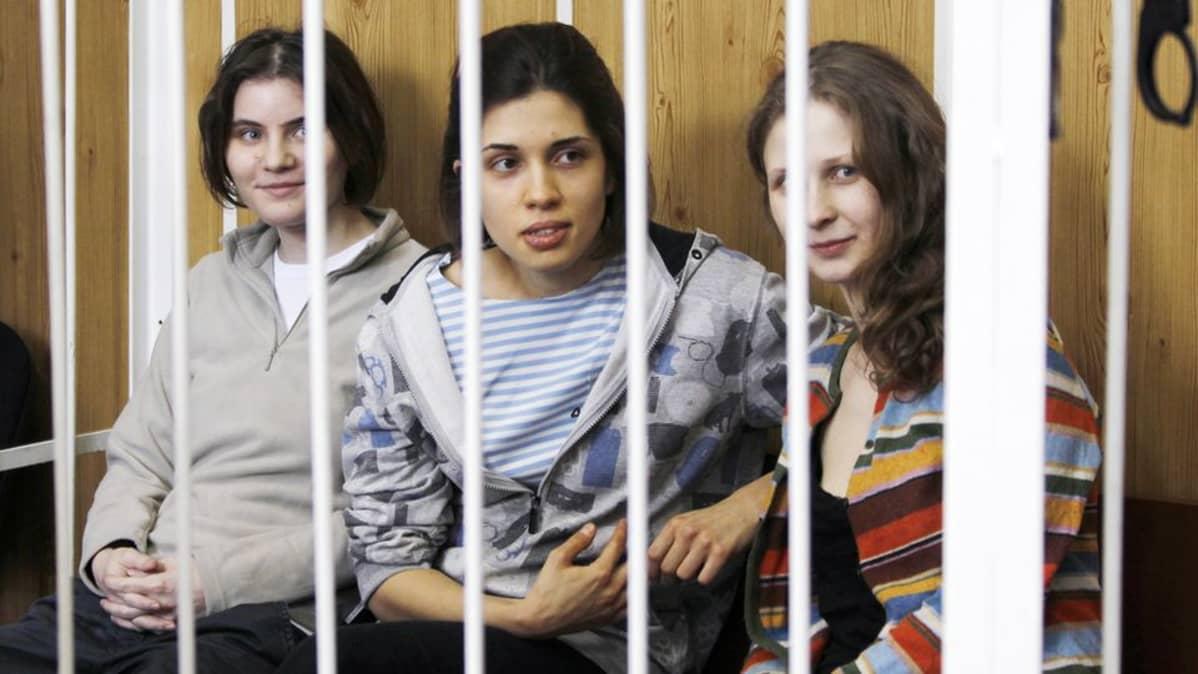 Syytettyinä olevat naiset kaltereiden takana oikeussalissa.