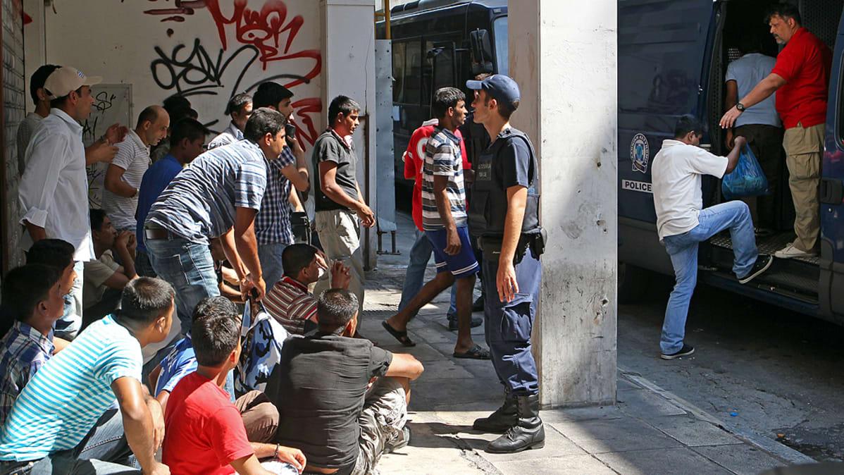Poliisi pidättää siirtolaisia.