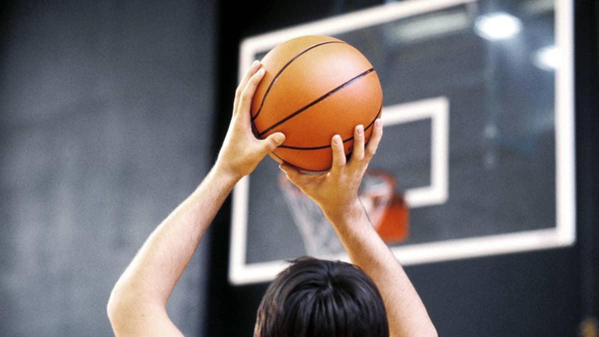 Poika heittää palloa koriin.