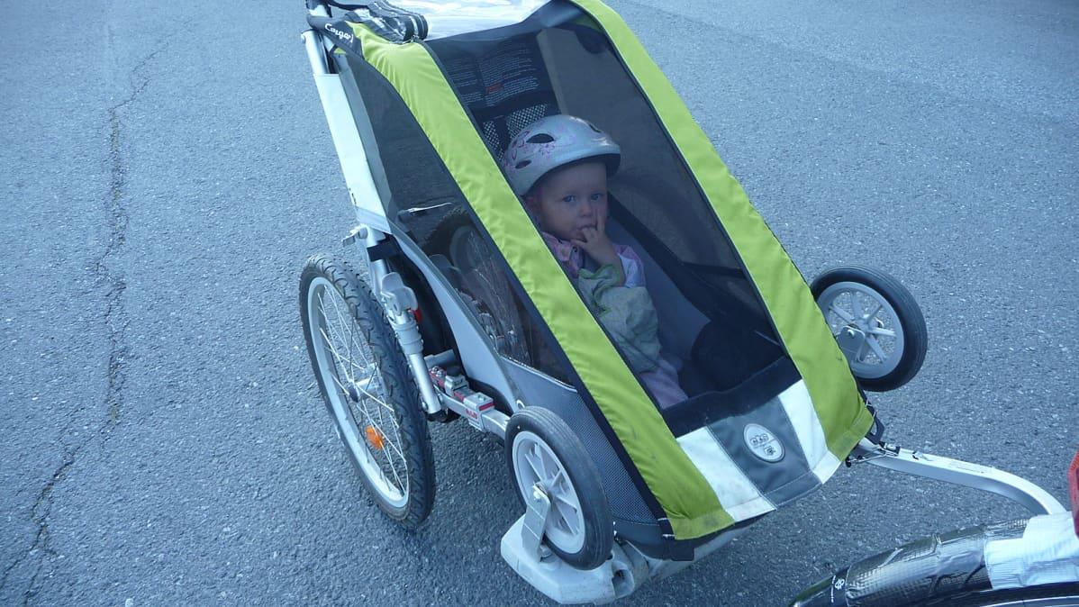 Pikkulapsi polkupyörän perävaunussa