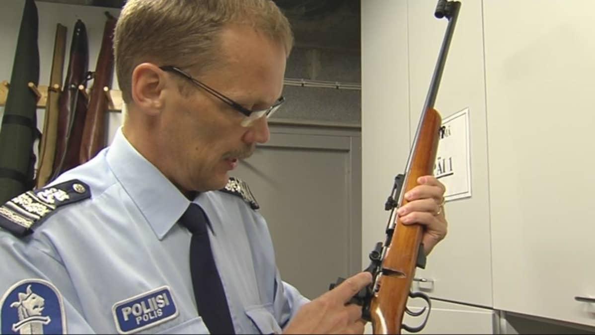 Ylikomisario Risto Jääskeläinen tutkii pienoiskivääriä poliisin asevarastossa.