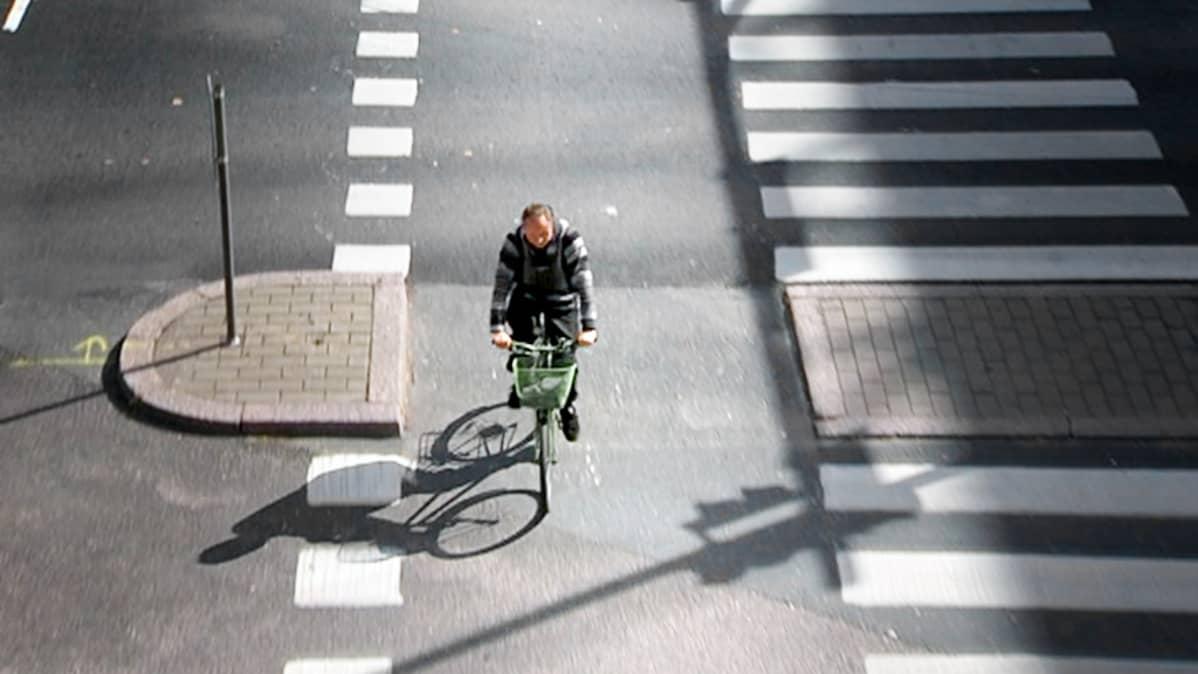 Mies ylittää polkupyörällä ajotietä.