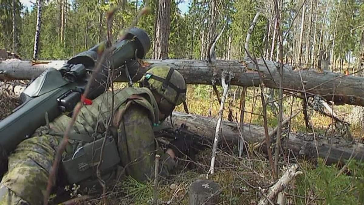 Sotilas väijyy puun takana.