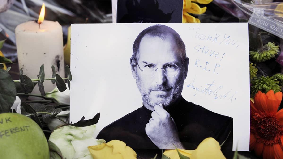 Kuva Steve Jobsista, muistokynttilä ja kukkia Lontoolaisen Apple-kaupan edustalla.