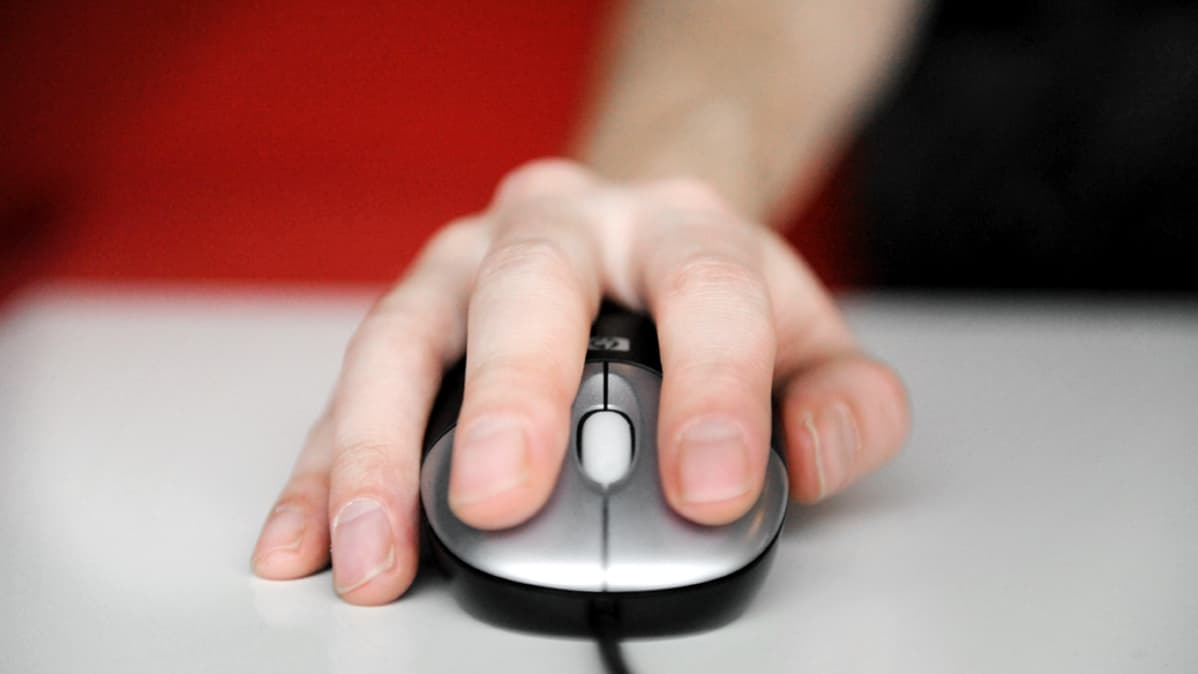 Käsi tietokoneen hiirellä.