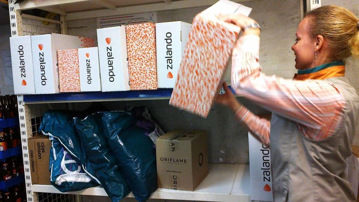 Työntekijä poimii pakettia hyllystä.