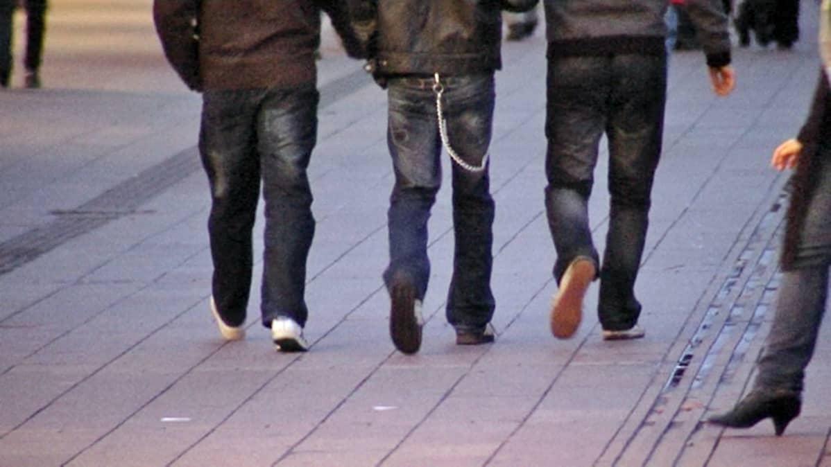Kolme nuorta miestä kävelee kadulla. Kuva takaapäin.