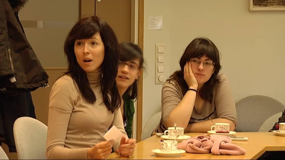 Kolme espanjalaista sairaanhoitajaa pöydän ääressä.