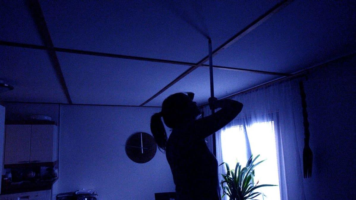 Nainen koputtaa kattoa harjalla.
