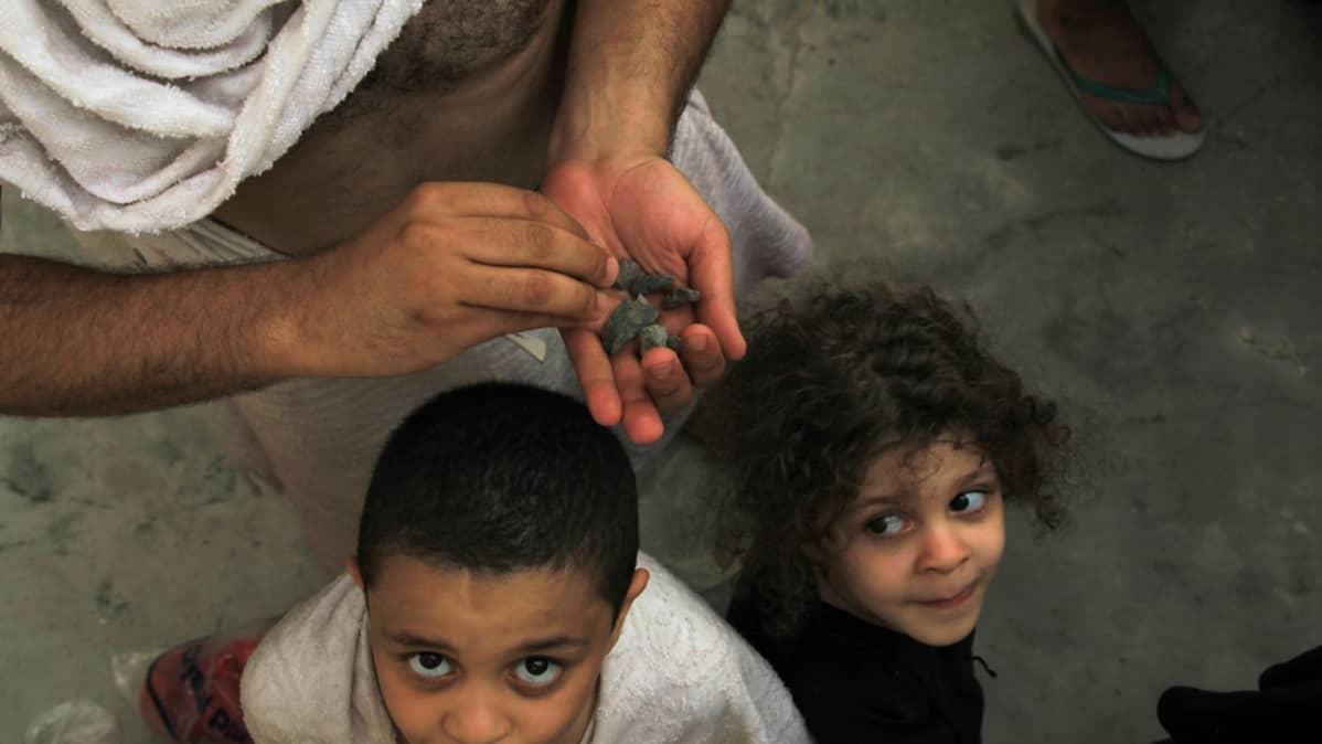 Viisi- ja nelivuotias sisaruspari katselee, kun heidän isänsä valmistautuu paholaisen kivittämiseen.