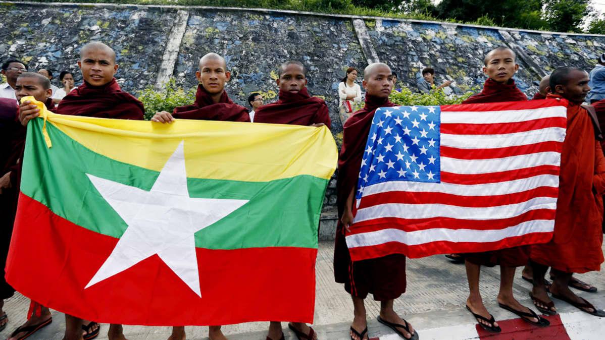Buddhistimunkit pitelevät Myanmarin ja Yhdysvaltain lippuja Yangon lentokentän edustalla.