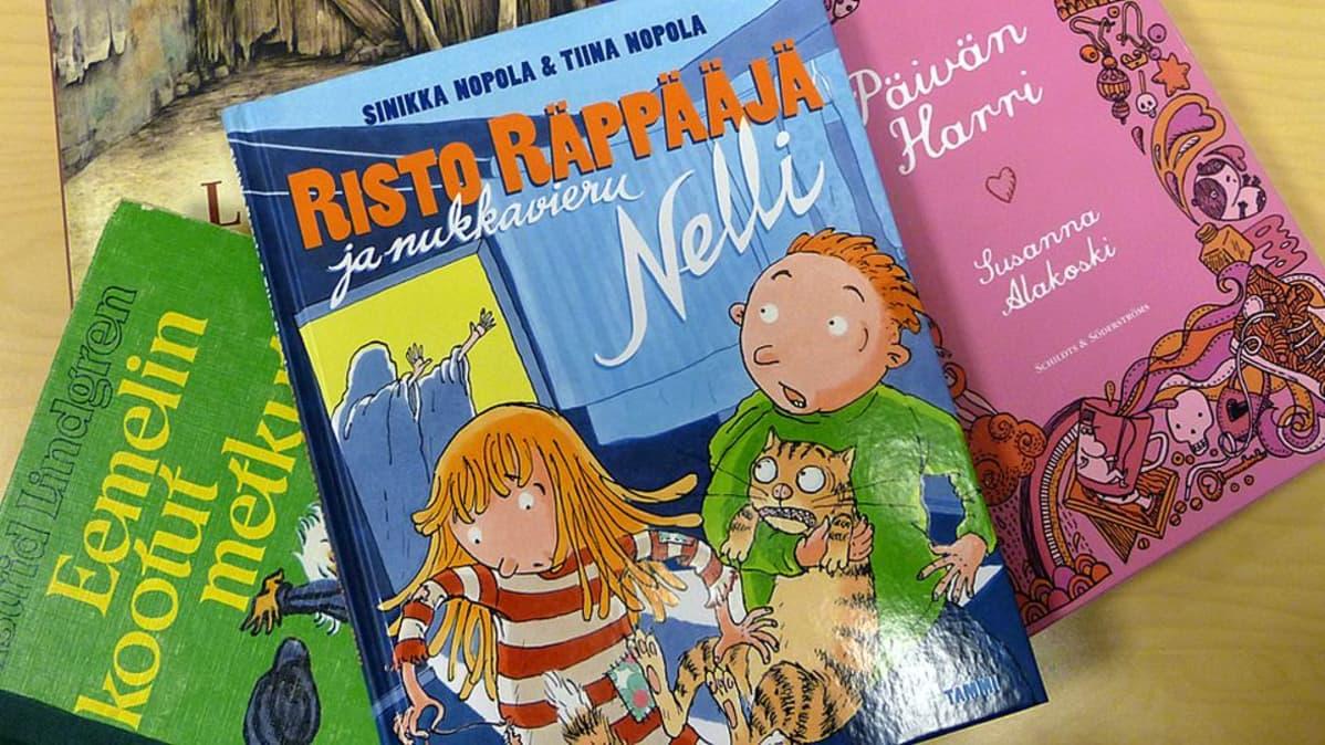Lastenkirjoja pinossa pöydällä