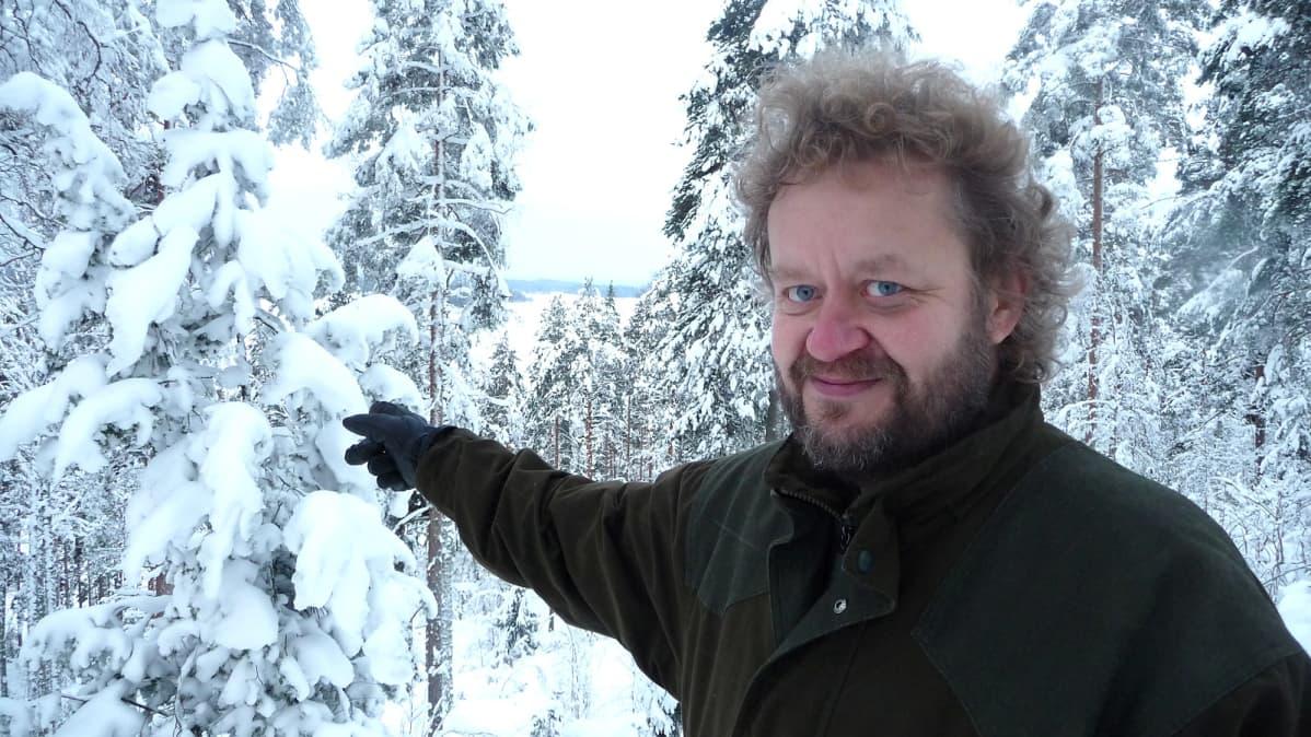 Mies lumisessa metsässä