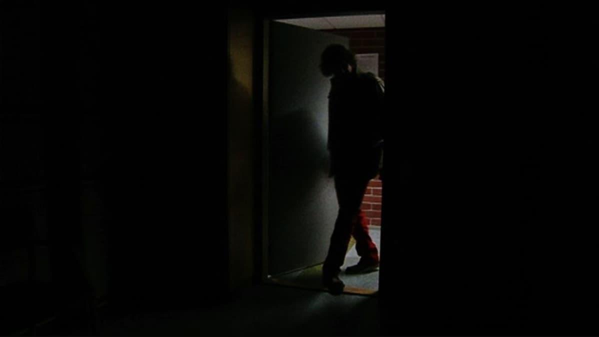 Henkilö astuu pimeään työhuoneeseensa.