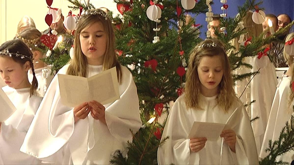 Kaksi enkeliksi pukeutunutta tyttöä lausuu jouluevankeliumia kuusen edessä.
