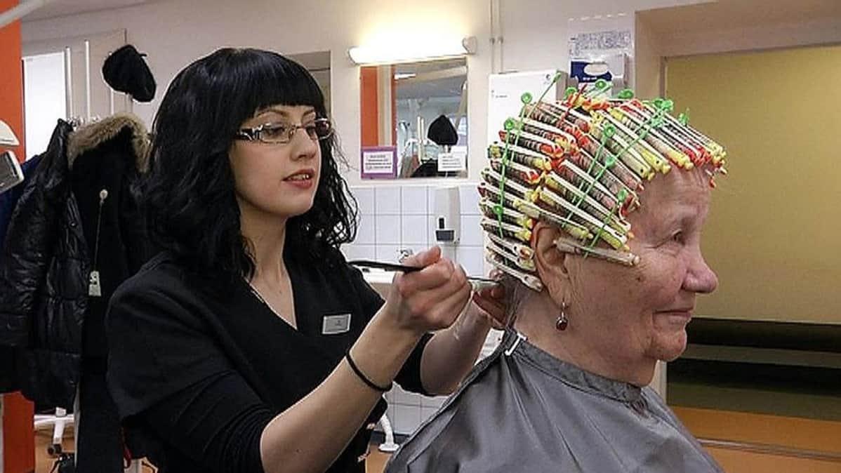 Kampaaja tekee hiusasiakkaalle permanenttia.