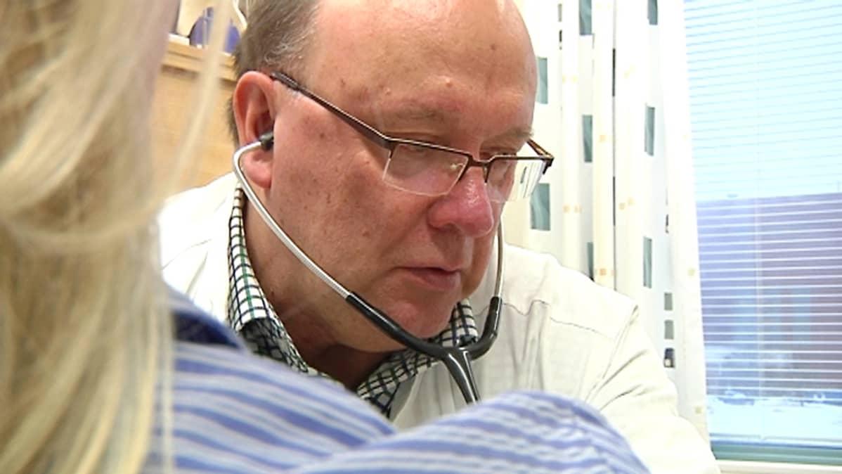 Boliden Kokkolan työterveyslääkäri Raimo Kerttula mittaa potilaan verenpainetta.
