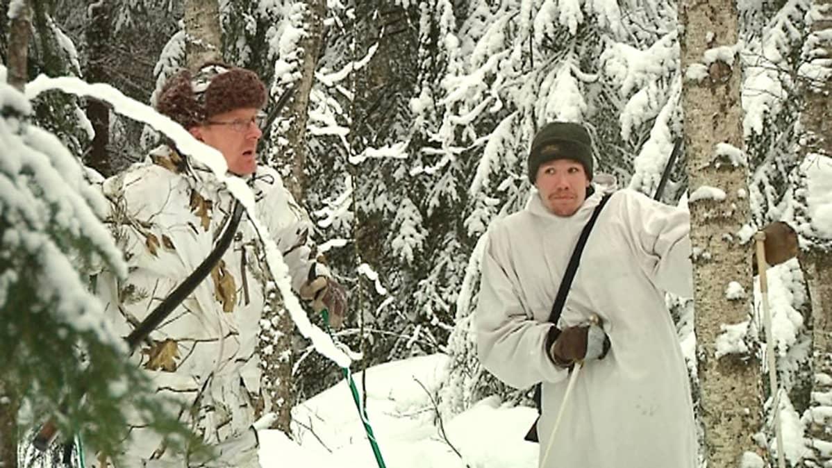 Kaksi miestä maastovaatteissa lumisessa metsässä